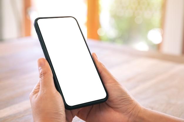 Makieta obrazu kobiecych rąk trzymających czarny telefon komórkowy z pustym białym ekranem na drewnianym stole