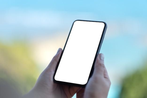 Makieta obrazu kobiecych rąk trzymających czarny telefon komórkowy z pustym białym ekranem z niewyraźnym tłem natury