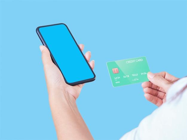 Makieta obrazu kobiety ręki trzymającej telefon komórkowy, pusty ekran i kartę kredytową