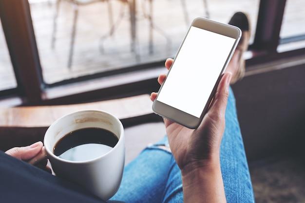 Makieta obrazu kobiety trzymającej biały telefon komórkowy z pustym ekranem pulpitu podczas siedzenia i picia kawy w kawiarni
