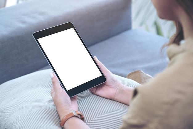 Makieta obrazu kobiety trzymającej czarny tablet pc z pustym białym ekranem pulpitu siedzącej w salonie z uczuciem relaksu
