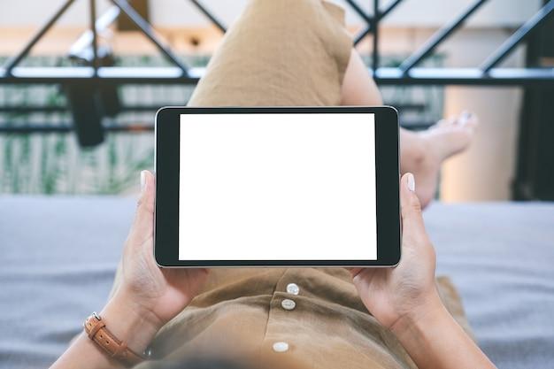 Makieta obrazu kobiety trzymającej czarny tablet z pustym białym ekranem, leżącej w salonie z uczuciem relaksu