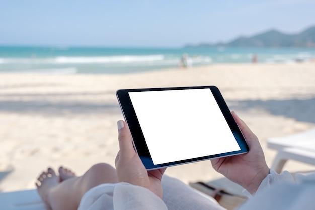Makieta obrazu kobiety trzymającej czarny tablet z pustym ekranem, leżąc na leżaku na plaży