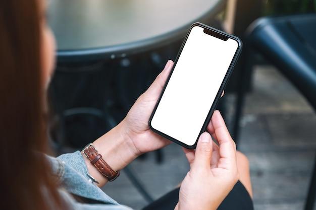 Makieta obrazu kobiety trzymającej czarny telefon komórkowy z pustym białym ekranem pulpitu