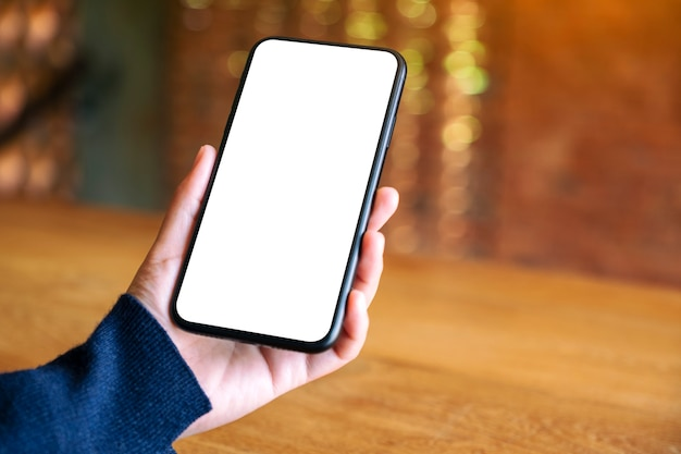 Makieta obrazu kobiety trzymającej czarny telefon komórkowy z pustym białym ekranem w kawiarni