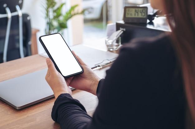 Makieta obrazu kobiety trzymającej czarny telefon komórkowy z pustym białym ekranem
