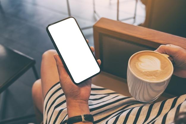 Makieta obrazu kobiety trzymającej czarny telefon komórkowy z pustym ekranem podczas picia kawy w kawiarni