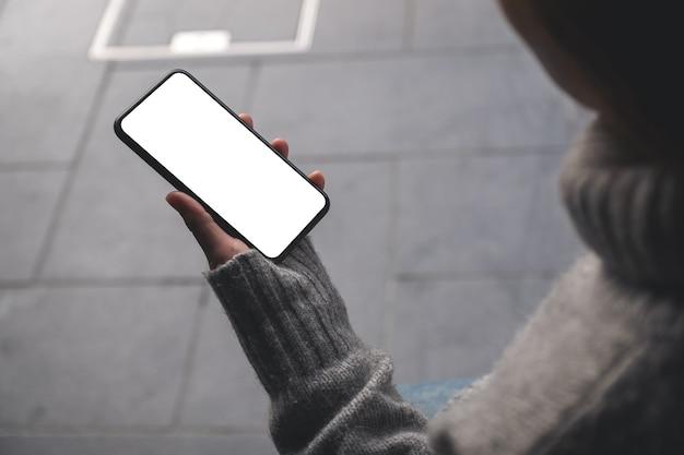 Makieta obrazu kobiety trzymającej czarny telefon komórkowy z pustym ekranem pulpitu na świeżym powietrzu