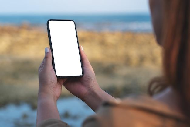 Makieta obrazu kobiety trzymającej czarny telefon komórkowy z pustym ekranem pulpitu przy plaży i morzu