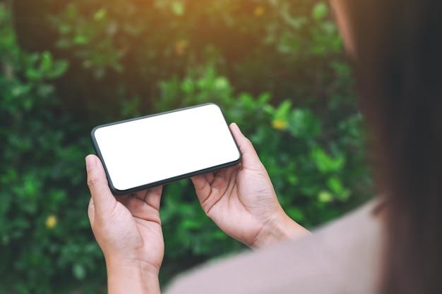 Makieta obrazu kobiety trzymającej czarny telefon komórkowy z pustym ekranem pulpitu z zielonym tłem przyrody