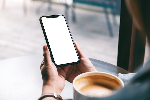 Makieta obrazu kobiety trzymającej czarny telefon komórkowy z pustym ekranem z filiżanką kawy na drewnianym stole