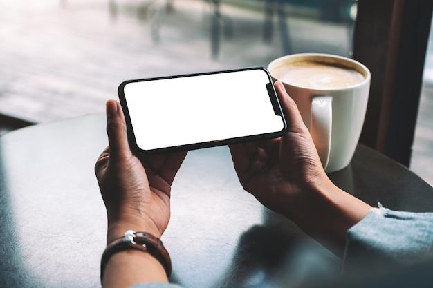 Makieta obrazu kobiety trzymającej czarny telefon komórkowy z pustym ekranem z filiżanką kawy na stole