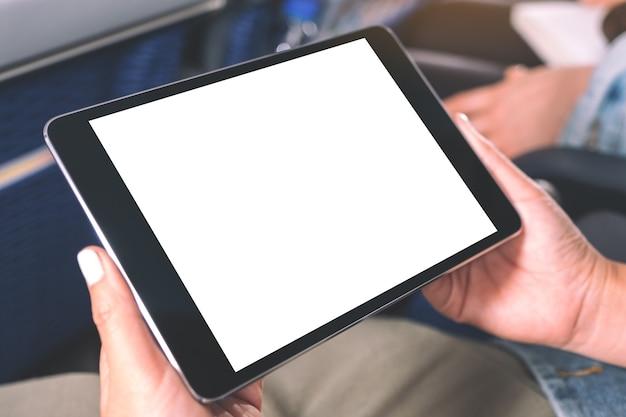Makieta obrazu kobiety trzymającej i patrząc na czarny tablet pc z pustym białym ekranem pulpitu siedząc w kabinie