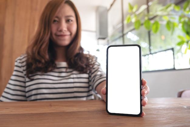 Makieta obrazu kobiety trzymającej i pokazującej biały telefon komórkowy z pustym ekranem na drewnianym stole