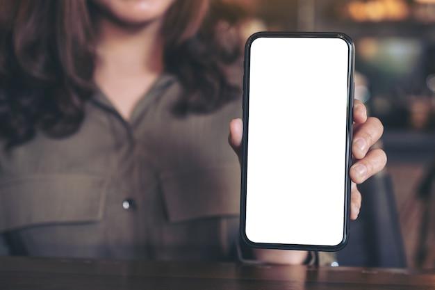 Makieta obrazu kobiety trzymającej i pokazującej czarny telefon komórkowy z pustym białym ekranem na stole w nowoczesnej kawiarni