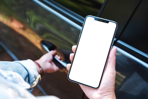 Makieta obrazu kobiety trzymającej telefon komórkowy i używającego go z pustym ekranem podczas otwierania drzwi samochodu