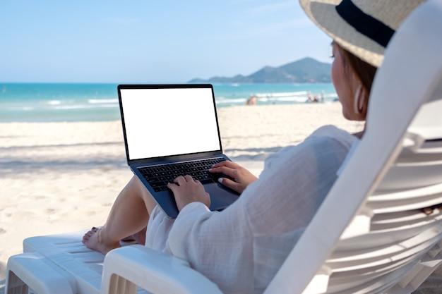 Makieta obrazu kobiety używającej i piszącej na komputerze przenośnym z pustym ekranem pulpitu, kładąc się na leżaku na plaży