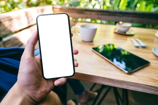 Makieta obrazu mężczyzny trzymającego czarny telefon komórkowy z pustym białym ekranem z kobietą w tle