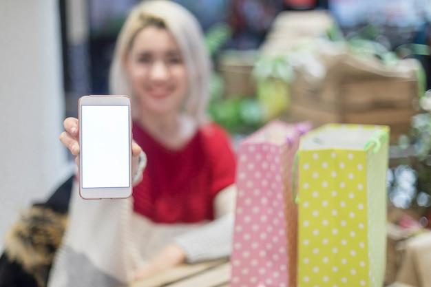 Makieta obrazu pięknej kobiety trzymającej i pokazującej biały telefon komórkowy z pustym białym ekranem z uśmiechniętą buźką i torby na zakupy