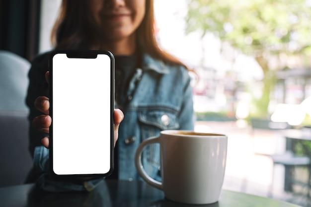 Makieta obrazu pięknej kobiety trzymającej i pokazującej czarny telefon komórkowy z pustym ekranem w kawiarni