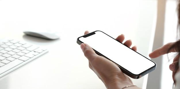 Makieta obrazu pusty biały ekran telefon komórkowy. kobiety ręka trzyma sms-y za pomocą telefonu komórkowego na biurku w domowym biurze.