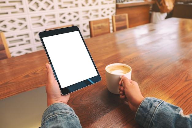 Makieta obrazu rąk trzymających czarny tablet pc z pustym białym ekranem podczas picia kawy na drewnianym stole
