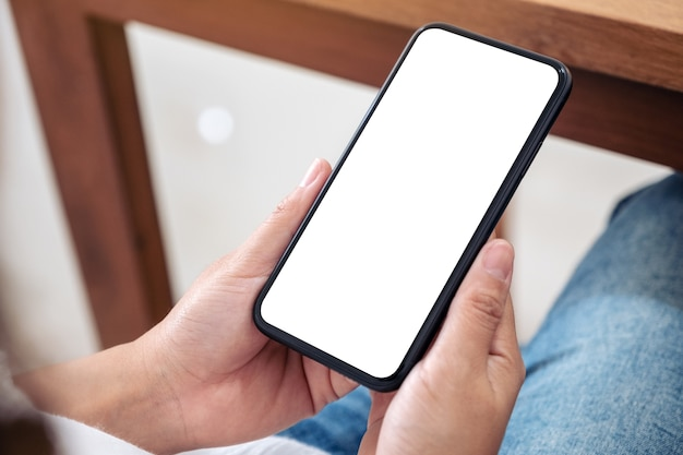 Makieta obrazu rąk trzymających czarny telefon komórkowy z pustym białym ekranem podczas siedzenia