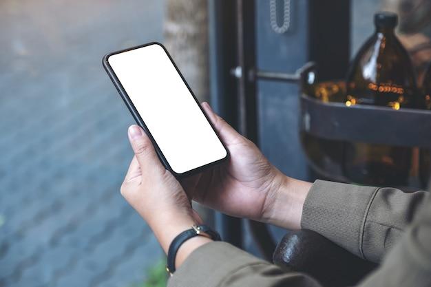 Makieta obrazu rąk trzymających czarny telefon komórkowy z pustym białym ekranem pulpitu