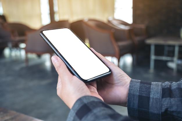 Makieta obrazu rąk trzymających czarny telefon komórkowy z pustym białym ekranem w kawiarni vintage