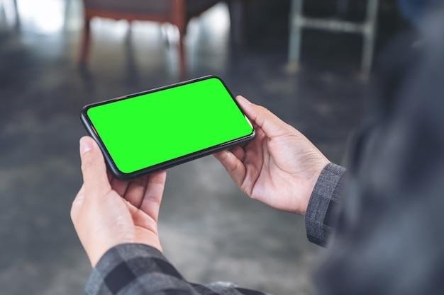 Makieta obrazu rąk trzymających czarny telefon komórkowy z pustym ekranem poziomo w kawiarni vintage