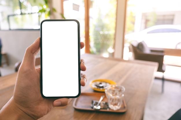 Makieta obrazu ręki mężczyzny trzymającego i pokazującego czarny telefon komórkowy z pustym białym ekranem, siedząc w kawiarni