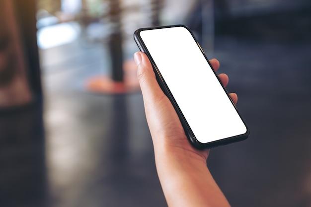 Makieta obrazu ręki trzymającej czarny telefon komórkowy z pustym białym ekranem pulpitu w kawiarni