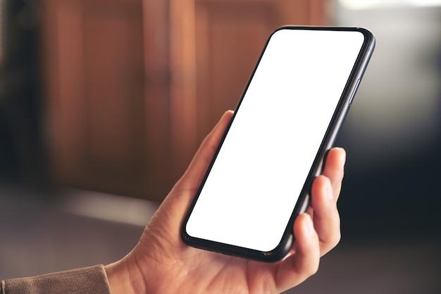 Makieta obrazu ręki trzymającej czarny telefon komórkowy z pustym białym ekranem pulpitu