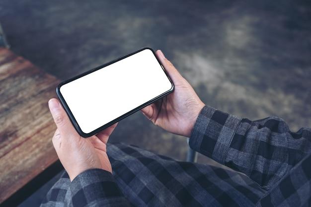 Makieta obrazu ręki trzymającej czarny telefon komórkowy z pustym białym ekranem