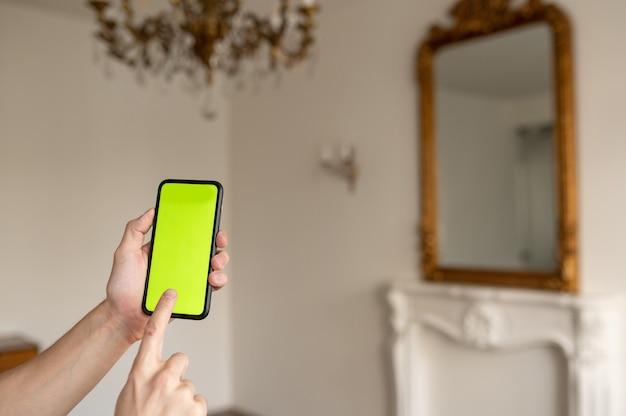 Makieta obrazu ręki trzymającej czarny telefon komórkowy z pustym zielonym ekranem i nowoczesnym wnętrzem tła