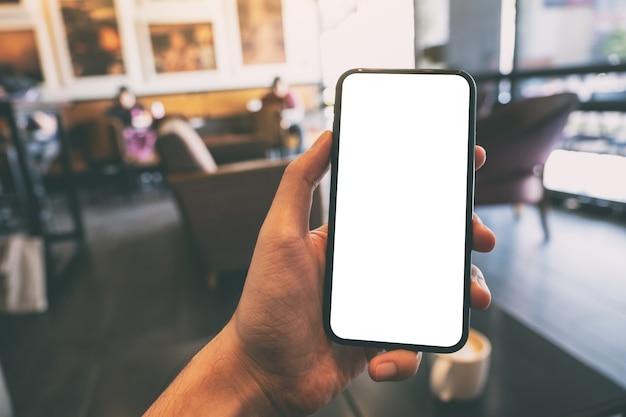 Makieta obrazu ręki trzymającej i pokazującej czarny telefon komórkowy z pustym białym ekranem w kawiarni