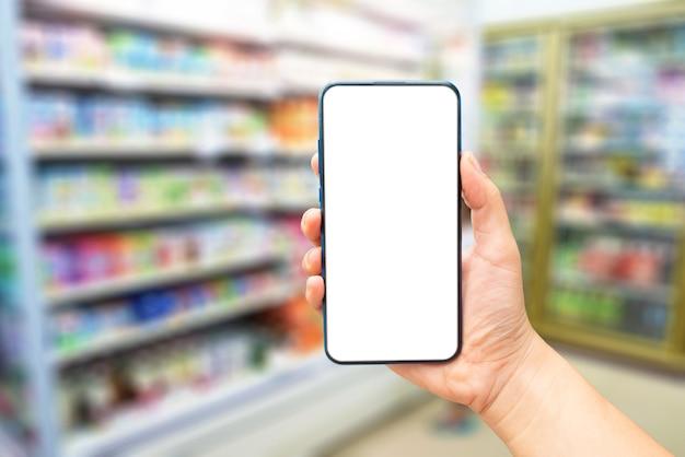 Makieta obrazu ręki trzymającej pusty ekran smartfona na rozmytym tle
