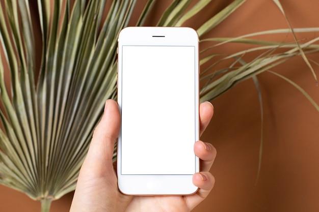 Makieta obrazu ręki trzymającej telefon komórkowy z pustym białym ekranem.