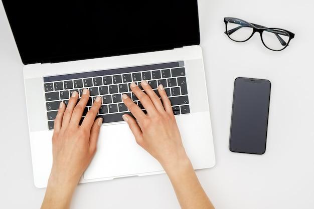 Makieta obszaru roboczego biura domowego. laptop z pustym ekranem, rękami i akcesoriami na bielu