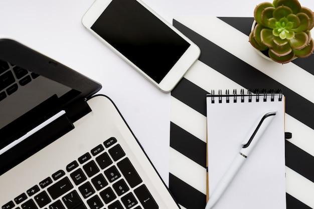 Makieta obszaru roboczego biura domowego z laptopem, soczystym doniczkiem, notatnikiem i akcesoriami. leżał płasko, widok z góry