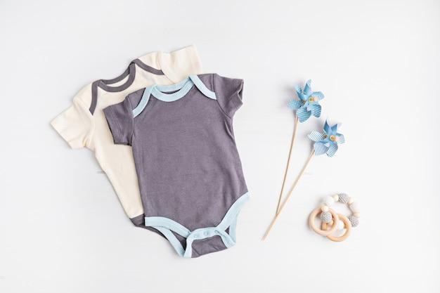 Makieta odzieży dziecięcej neutralnej pod względem płci. ubrania z bawełny organicznej, moda noworodkowa, branding, pomysł na mały biznes. płaski układanie, widok z góry