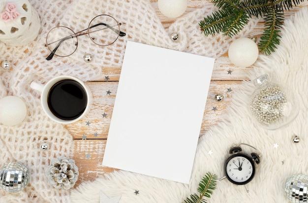 Makieta okładki magazynu płaska leżała z filiżanką czarnej kawy, budzikiem, dekoracją świąteczną i gałązkami jodły
