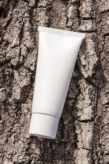 Makieta opakowania produktów kosmetycznych. organiczny krem kosmetyczny w tubie na naturalnej ścianie kory drzewa. butelka z kremem, balsam, mus, szampon do rutynowej pielęgnacji skóry.