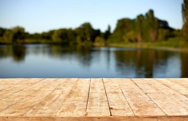 Makieta. opróżnia drewnianego pokładu stół z ulistnienia bokeh tłem.