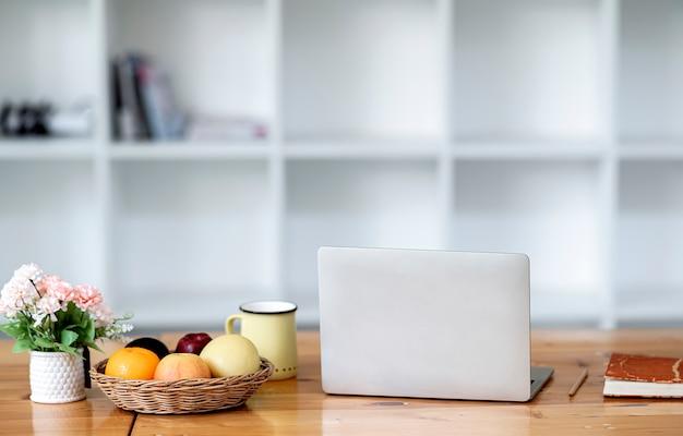 Makieta owoców i laptopa na stole.