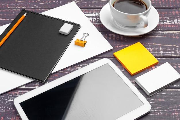 Makieta papeterii na fioletowym biurku. widok z góry papieru, wizytówki, podkładki, długopisy i kawy.