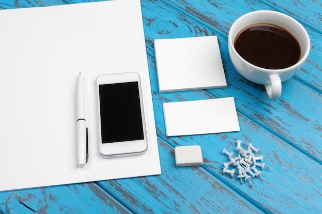 Makieta papeterii na niebieskim biurku. widok z góry papieru, wizytówki, podkładki, długopisy i kawy.