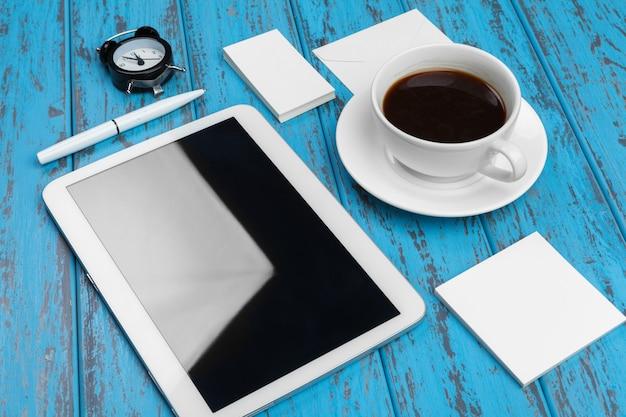 Makieta papeterii na niebieskim biurku. widok z góry tabletu, wizytówki, podkładki, długopisy i kawy.