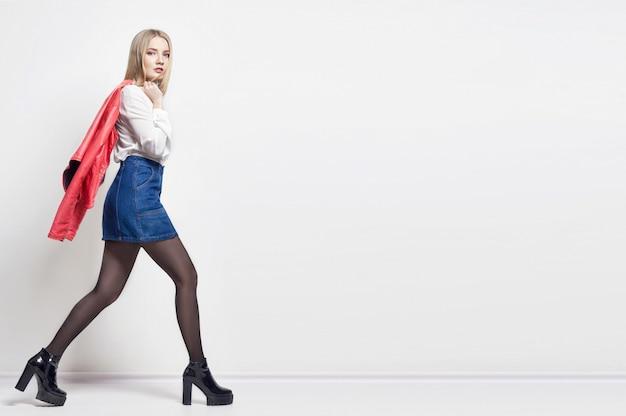 Makieta Piękna Seksowna Blond Kobieta W Koszuli I Spódnicy. Dziewczyna Z Idealnym Ciałem, Pozowanie Na Stojąco. Piękne Długie Włosy I Nogi, Gładka, Czysta Skóra Premium Zdjęcia