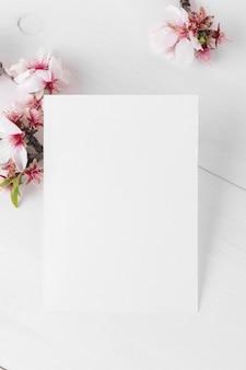 Makieta pionowej pustej karty z kwitnącą gałąź drzewa migdałowego
